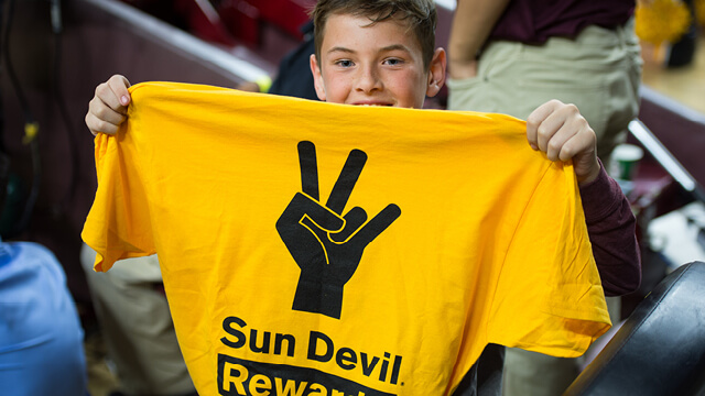 kid holding Sun Devil Rewards shirt