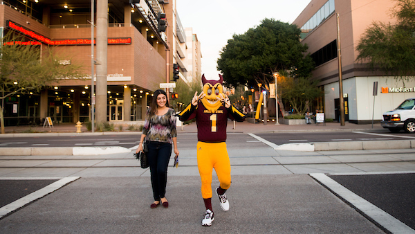 ASU student walking with Sparky